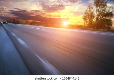 Asphalt countryside road in motion with truck and cars against night sky with bright sunset