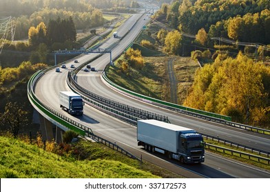 Asphalt highway with electronic toll gates in autumn woodland. Three trucks on the road. The bridge spanning the valley. View from above. Sunny day with bright fall colors.