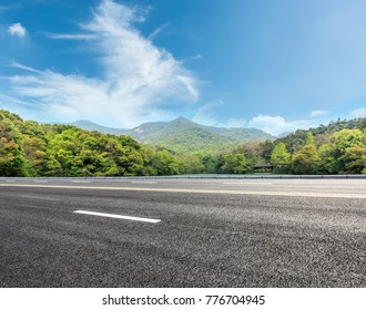 asphalt highway and green mountain nature landscape under blue sky