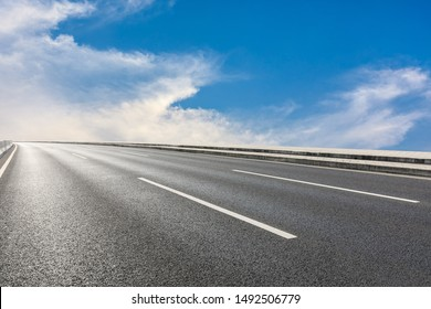 Asphalt highway road and blue sky with white clouds