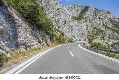 Asphalt highway in a sunny day outside the city passing through the cliff.