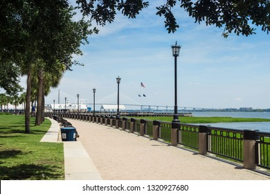 Asphalt path in the park along the bay. Walkway in the summer park with lanterns and green trees near the ocean. Joe Riley Waterfront Park. Charleston, SC / USA - July 21 2018