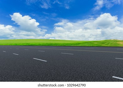 Asphalt pavements and prairies under the blue sky and white clou