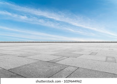 Asphalt pavements and square floor tiles under the blue sky and white clouds