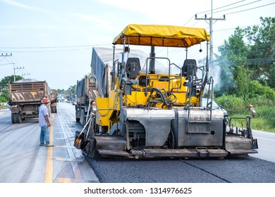 Asphalt paver machine on the road construction site.