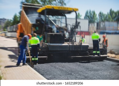 Asphalt paver machine and steam road roller during road construction and repairing works, process of asphalting and paving, workers working on the new road construction site, placing a layer, drone