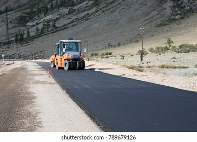 Asphalt paver of orange color rolls black asphalt for a road in the mountains in summer