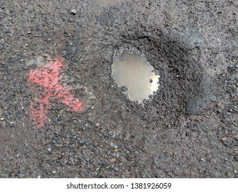 Asphalt Pothole Filled with Dirty Water Puddle in a Parking Lot or Road / Highway with a Red X Spray Painted Next to It on the Blacktop