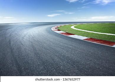Asphalt race track with dramatic turning curve corner.