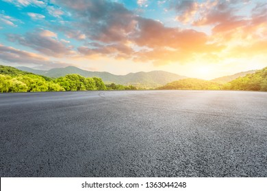 Asphalt race track ground and mountains with beautiful clouds at sunset
