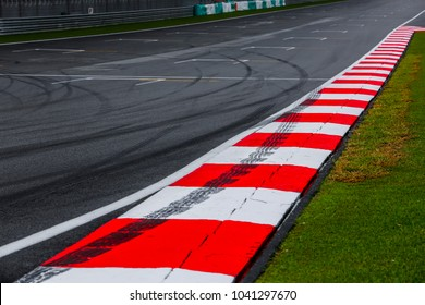 Asphalt red and white kerb of a race track detail with tire marks. Motorsports racing circuit close up.