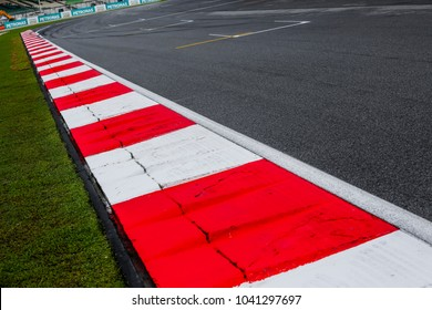 Asphalt red and white kerb of a race track detail. Motorsports racing circuit close up.