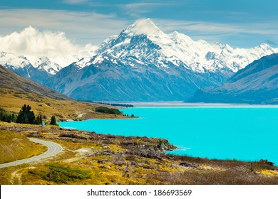 asphalt road along Lake Pukaki view from Glentanner Park Centre near Mount Cook; on a background of blue sky with clouds; snowy Southern Alps.