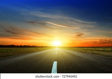 Asphaltstraße zwischen den Feldern bei Sonnenuntergang