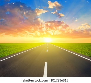 asphalt road among a green fields leaving far avay at the sunset