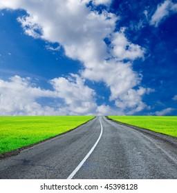 asphalt road among green fields