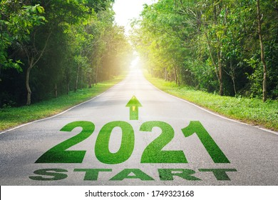 Asphalt road with arrow guideline and 2021 letters painted on the surface , Start of the new year 2021. The number 2021 on a empty Country road in a beautiful landscape. New Year concepts