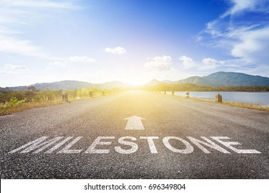 Asphalt road with arrow guideline and Milestone letters painted on the surface. An image of a road milestones are representative of success in the future goal. Road to success with light of the sun