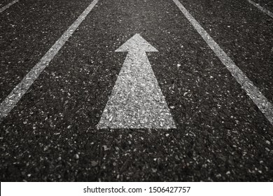 Asphalt road with an arrow pointing forward on the surface. An image of a milestone roadmap is a representation of success in the future goal