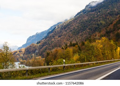 Asphalt road in autumn at sunrise. Landscape with beautiful empty mountain road with a perfect asphalt, high rocks, trees and sunny sky. Vintage toning. Travel background. Highway at mountains. Speed