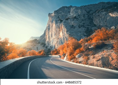 Asphalt road in autumn at sunrise. Landscape with beautiful empty mountain road with a perfect asphalt, high rocks, trees and sunny sky. Vintage toning. Travel background. Highway at mountains. Nature