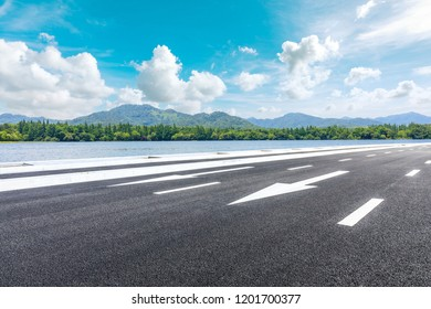 Asphalt road and beautiful mountain with lake under the blue sky