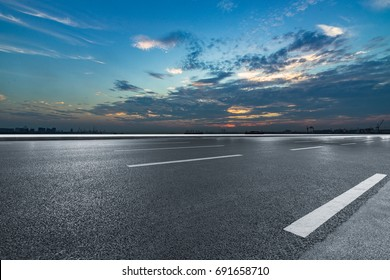 Asphalt road and the beautiful urban skyline at sunset