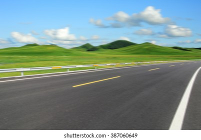 Asphalt road beside green meadow under blue sky.