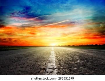 Asphalt road between fields  trees