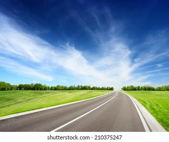 Asphalt road between grassy meadow with trees on horizon. Summer landscape with blue sky