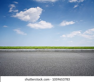 Asphalt road and blue sky above green grass