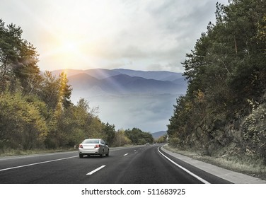Asphalt road and cars in the mountains with cloudy sky on the background.