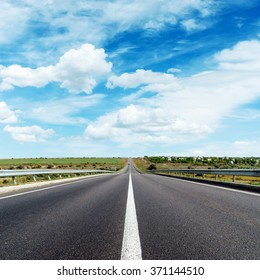 asphalt road with central white line under cloudy sky