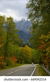 Asphalt road in colorful autumn forest against mountain.