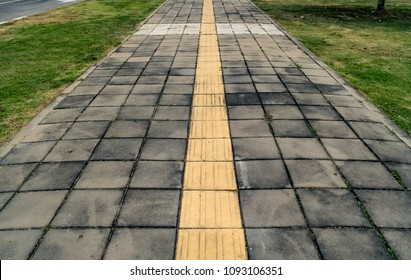 Asphalt road and Concrete block sidewalk with Red and white concrete curb