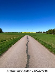Asphalt road with a crack in the middle along green fields a beautiful spring day with clear blue sky and green trees on the side of a rapeseed meadow.