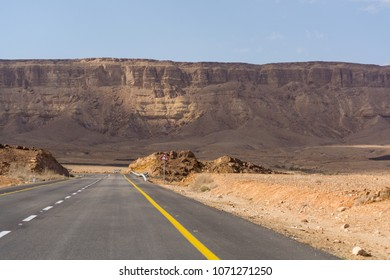 Asphalt road in desert Negev, Israel, road 40, transport infrastructure in desert, scenic mountains route in Mizpe Ramon canyon in Israel