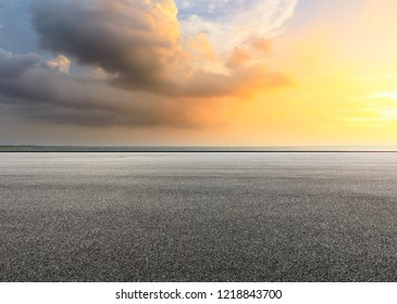 Asphalt road and dramatic sky with coastline at sunset