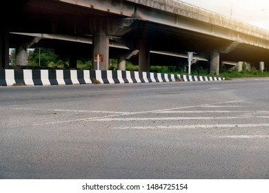 The asphalt road is empty and there are bridges of different levels in the background.