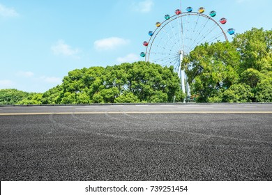Asphalt road and ferris wheel playgrounds with green tree in the city park