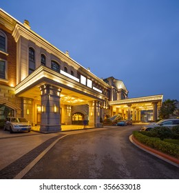 asphalt road front of luxury hotel in clear sky at night