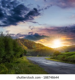 asphalt road going to mountain, passes rural places at ominous sunset after the rain