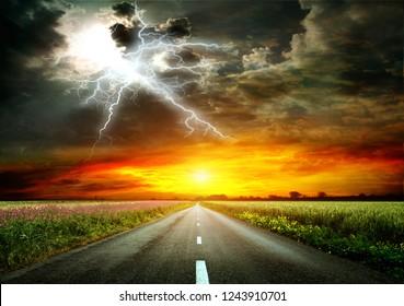 Asphalt Straße durch ein Feld von Weizen und Alfalfa. Am Horizont, Sonnenuntergang und Blitz. Die Natur vor einem Gewitter. Sehr helles Bild