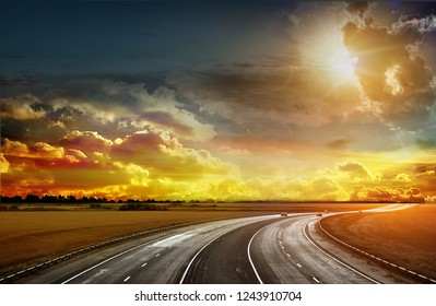 Asphalt road going through a field of wheat and alfalfa. Sunset on the horizon. Nature before a thunderstorm. Very bright image