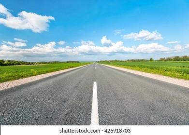 Asphaltstraße auf grünen Feldern auf blauem, bewölktem Himmelshintergrund. Mehrfarbiges, dynamisches Außenbild.