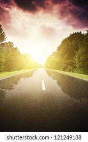 Asphalt road in green forest. Belarus. Storm blue sky.