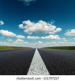asphalt road to horizon in deep blue cloudy sky