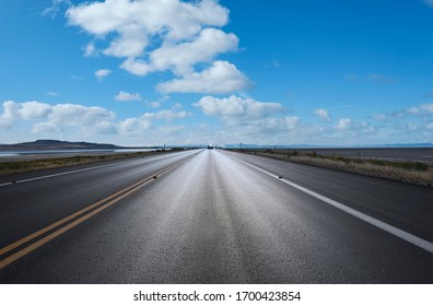 Asphalt road to the horizon line under blue sky with cotton clouds