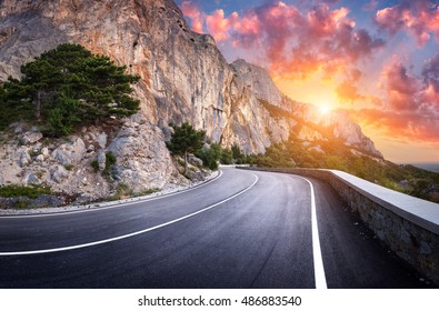 Asphalt road. Landscape with beautiful winding mountain road with a perfect asphalt in the evening. High rocks, amazing sky at sunset in summer. Panoramic. Travel background. Highway at mountains