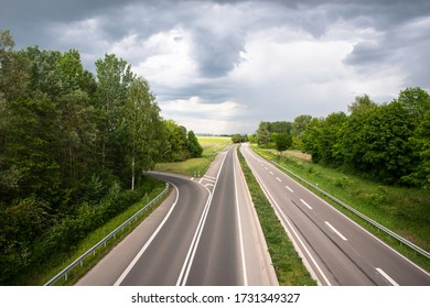 Asphalt road landscape, highway surrounded by lush green with a cloudy sky